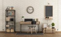 Písací stôl a okrúhle nástenné hodiny vo svetlej pracovni s tehlovou stenou