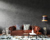 Hnedá kožená pohovka a biele dekorácie v kontraste s tmavosivou stenou