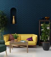 Žltá látková pohovka v kontraste s modrosivou tehlovou stenou