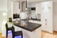 Moderná biela kuchyňa s čiernou pracovnou doskou