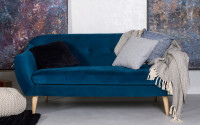 Modrá pohovka so sivými vankúšmi a dekou