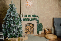 Vianočný stromček a girlanda s bielymi dekoráciami v klasickej obývačke s krbom a béžovou stenou