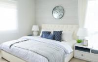 Biela čalúnená posteľ a okrúhle nástenné hodiny