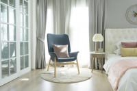 Sivé kreslo a biela čalúnená manželská posteľ