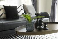 Okrúhly kovový stolík a čierne vázy v škandinávskom štýle