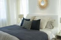 Biela čalúnená posteľ a okrúhle nástenné zrkadlo