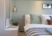 Posteľ s dekoračnými vankúšmi vo svetlosivej spálni