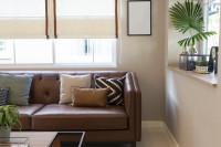 Hnedá kožená pohovka s dekoračnými vankúšmi