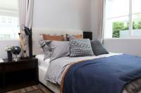 Pohodlná čalúnená posteľ s množstvom vankúšov