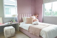Čalúnená posteľ v ružovo - bielej detskej izbe