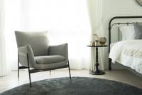 Sivé kreslo v spálni s bielou tehlovou stenou