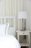 Kovová lampa a drevený nočný stolík v bielej spálni