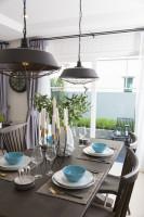 Hnedý jedálenský stôl a industriálne lampy