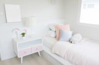 Posteľ a nočný stolík v modernej bielej detskej izbe