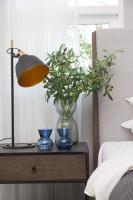 Moderný nočný stolík a sivá kovová lampa