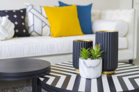 Čierne vázy a okrúhle stolíky v modernej obývačke
