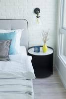 Okrúhly odkladací stolík v spálni s tehlovou stenou