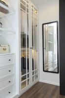 Nástenné zrkadlo s čiernym rámom v bielom šatníku