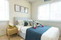 Čalúnená posteľ vo svetlej študentskej izbe