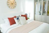 Nástenné hodiny nad bielou posteľou s pestrými vankúšmi