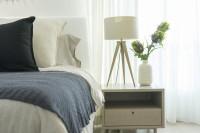 Nočný stolík a biela lampa vo svetlej spálni