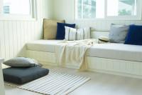Biela drevená posteľ s dekoračnými vankúšmi