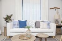 Biela pohovka s modrými vankúšmi a okrúhle stolíky