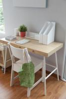 Drevený písací stôl a biela stolička vo svetlej pracovni