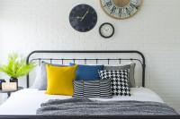 Čierna kovová posteľ a nástenné hodiny na tehlovej stene