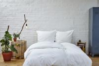 Manželská posteľ v industriálnej spálni s bielou tehlovou stenou