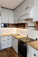 Biela kuchynská linka s profilovanými dvierkami a kovovými úchytkami