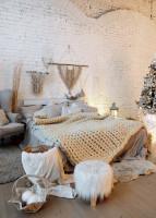 Posteľ s pletenou dekou v izbe s bielou tehlovou stenou