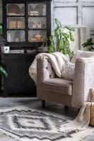 Čierna vintage komoda a svetlé kreslo s pletenou dekou