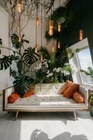 Svetlá pohovka a izbové rastliny v bohémskej obývačke