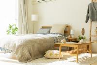 Drevený stolík a posteľ v škandinávskej spálni