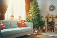 Svetlá pohovka s dekoračnými vankúšmi a veľký vianočný stromček v klasickej obývačke s tehlovou stenou