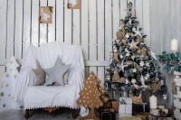 Biele kreslo a vianočný stromček s prírodnými dekoráciami