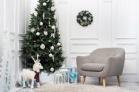 Sivé kreslo a vianočný stromček s bielymi dekoráciami