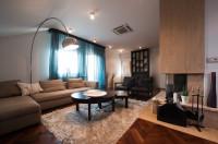 Béžová rohová sedačka a kovová stojanová lampa v modernej obývačke