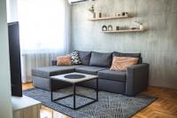 Sivá rohová pohovka a betónová stena v modernom štýle