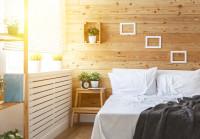Manželská posteľ vo svetlej drevom obloženej spálni