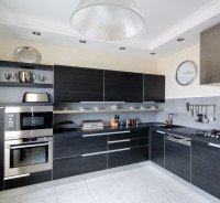 Čierna kuchynská linka a okrúhle nástenné hodiny