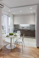 Okrúhly jedálenský stôl a biele stoličky v modernej kuchyni