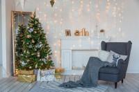 Vianočný stromček so zlatými dekoráciami a sivé kreslo ušiak