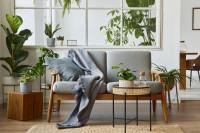 Sivá pohovka s dekou a okrúhly odkladací stolík