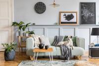 Svetlá pohovka s dekou a stolík v škandinávskom štýle