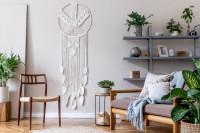 Elegantná drevená stolička a biela boho dekorácia na stenu