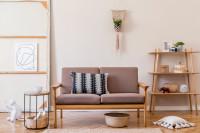 Pohovka vo svetlej obývačke s drevenými doplnkami