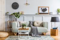 Malý stolík a svetlá pohovka s vankúšmi a dekou