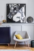 Sivé kreslo a nízka komoda v modernom štýle